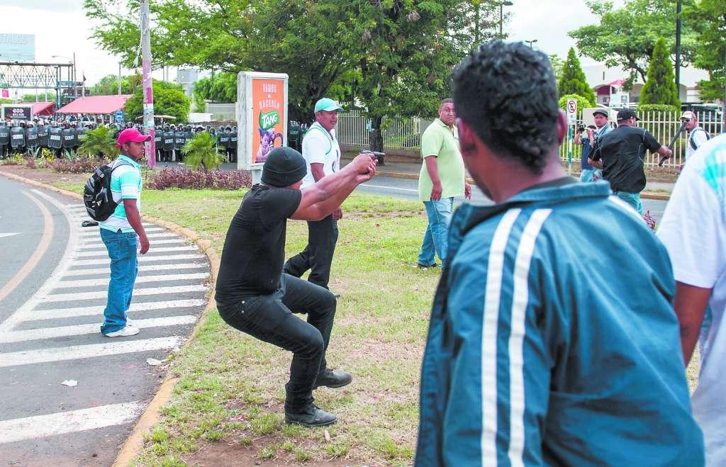 Un paramilitar al servicio de Ortega dispara contra manifestantes desarmados en pleno centro de Managua, en septiembre 2015
